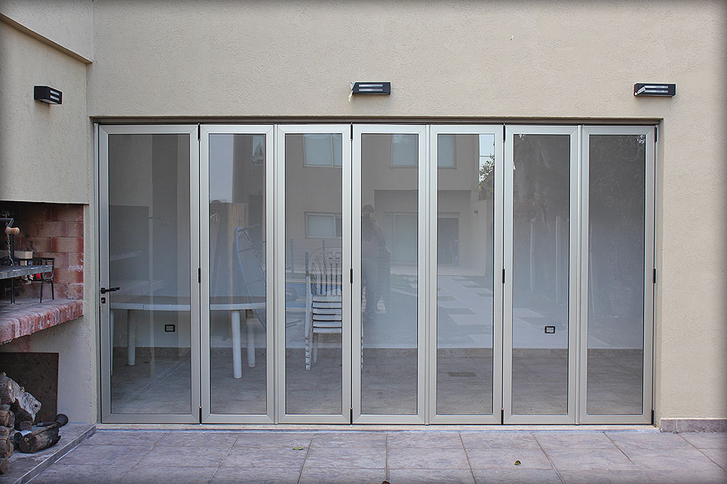 Puertas plegadizas batlo carpinteria de aluminio for Puertas de aluminio a medida precios